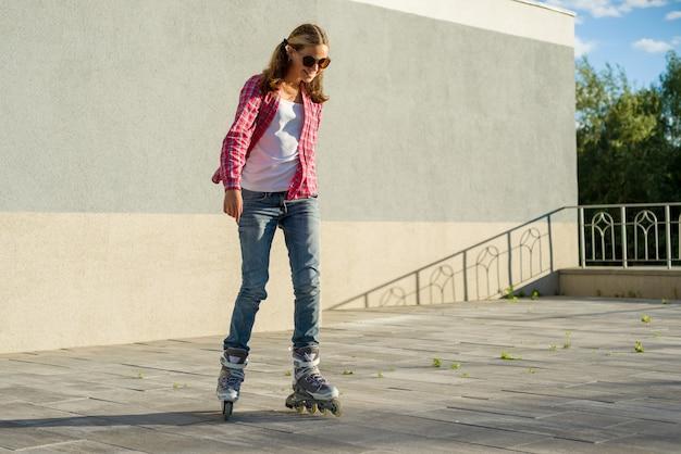 Il giovane adolescente sorridente della ragazza si diverte sui pattini di rullo
