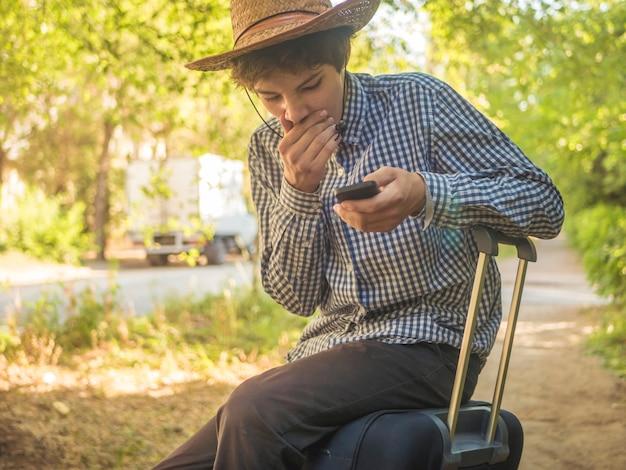 Il giovane adolescente turistico si siede sul grande caso della borsa di viaggio facendo uso del suo telefono cellulare