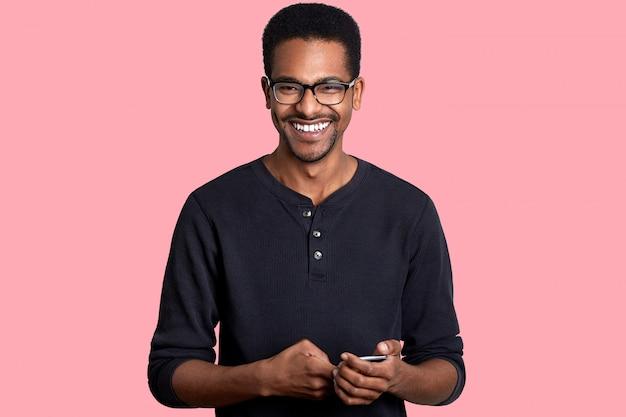 Il giovane afroamericano bello tiene lo smart phone con il sorriso, ha grandi notizie dall'amico. il modello dalla pelle scura posa sul rosa. concetto di persone e tecnologia.