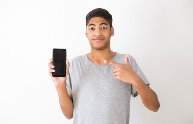Il giovane afroamericano mostra lo smartphone. copia spazio
