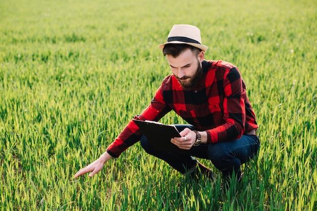 Il giovane agricoltore barbuto bello con la cartella analizza il raccolto nel giacimento di grano di inizio dell'estate