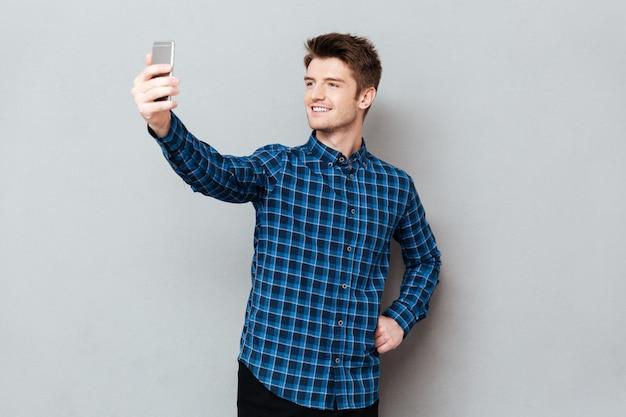 Il giovane allegro che controlla la parete grigia e fa il selfie