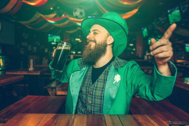 Il giovane allegro felice si siede alla tavola in pub. indossa un completo verde di san patrizio. guy indica in avanti.
