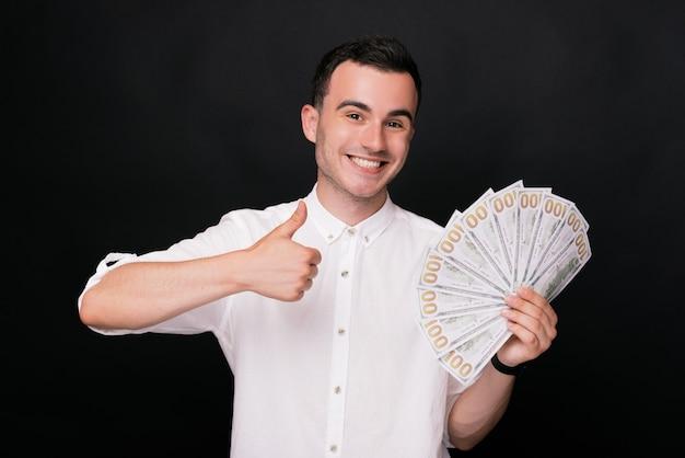 Il giovane allegro mostra il pollice sul gesto e con un'altra mano che tiene alcuni dollari
