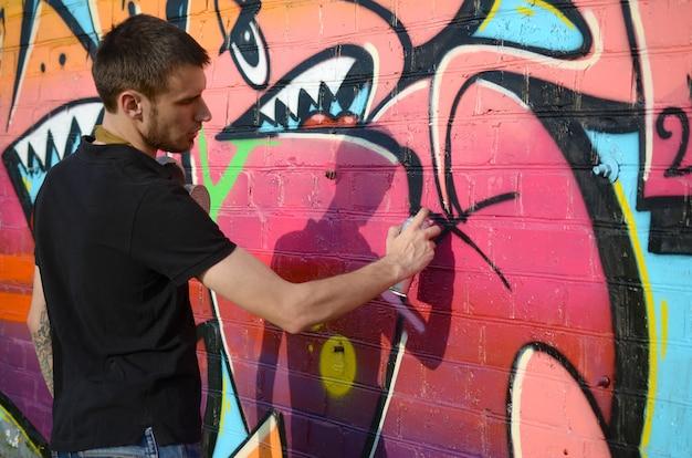 Il giovane artista dei graffiti con lo zaino e la maschera antigas sul suo collo dipinge i graffiti variopinti nei toni rosa sul muro di mattoni. arte di strada e processo di pittura contemporanea