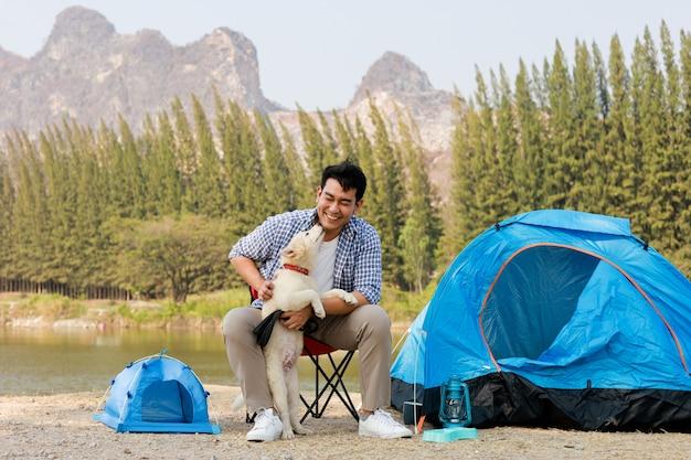 Il giovane asiatico in camicia blu con il cucciolo di cane sveglio che si accampa sul mountain view della collina del lago felice e gode della vita