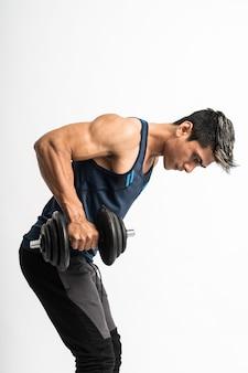 Il giovane asiatico solleva il manubrio per allenare i muscoli della schiena e i tricipiti