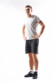 Il giovane atleta maschio va nello sport nello studio, atleta muscolare gonfiato