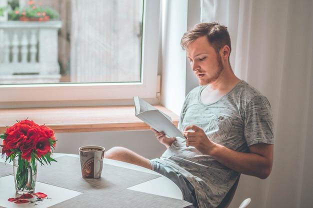 Il giovane attraente sta leggendo un libro a casa