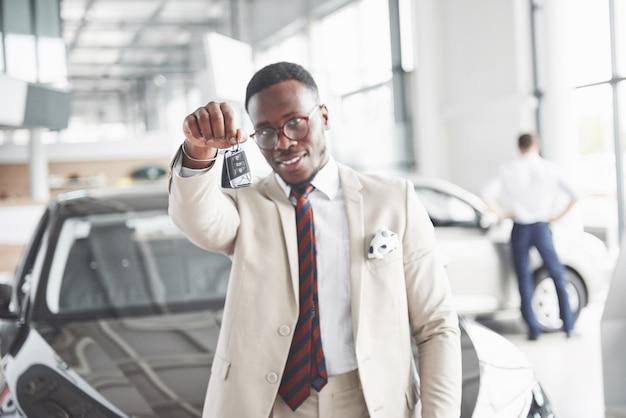 Il giovane attraente uomo d'affari nero acquista una nuova macchina, i sogni diventano realtà.