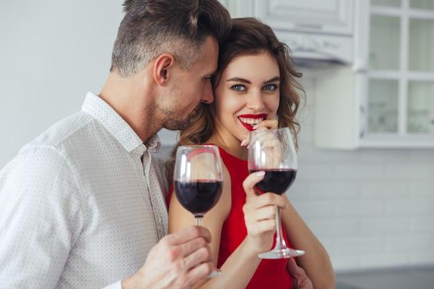 Il giovane bacia la sua bella donna sorridente mentre beve il vino