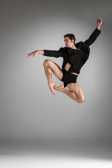 Il giovane ballerino di balletto moderno attraente che salta sul fondo bianco