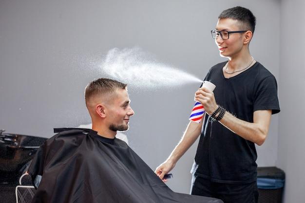 Il giovane barbiere kazako lavora in un barbiere, un giovane fa un taglio di capelli corto da un parrucchiere, si bagna la testa