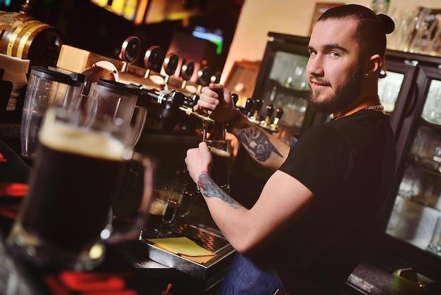 Il giovane barista attraente dell'uomo versa la birra nella tazza e esamina la macchina fotografica