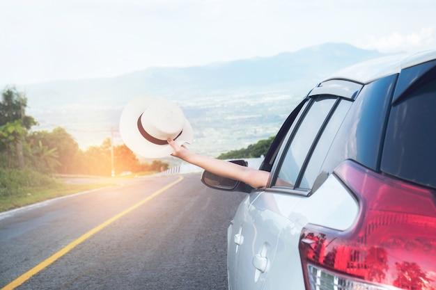 Il giovane bello cappello asiatico della tenuta della ragazza tessuto e raggiunge dall'auto al tramonto