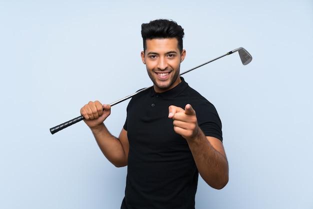 Il giovane bello che gioca il golf sopra la parete blu isolata indica il dito voi con un'espressione sicura