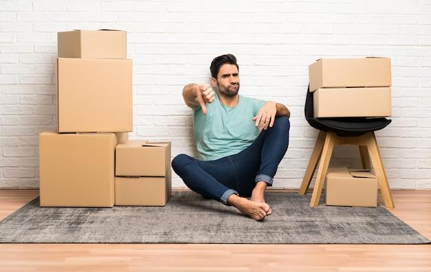 Il giovane bello che si muove nella nuova casa fra le scatole che mostrano il pollice giù firma