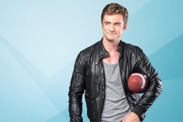 Il giovane bello in abbigliamento casual sta tenendo una palla di football americano