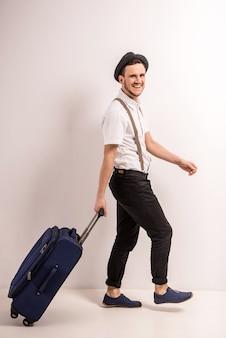 Il giovane bello in cappello sta camminando con la valigia.