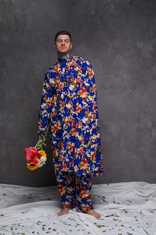 Il giovane bello in vestiti floreali che tengono la gerbera fiorisce a disposizione contro la parete grigia