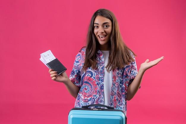 Il giovane bello passaporto della tenuta della donna del viaggiatore ed i biglietti usciti e la diffusione allegra consegna la parete rosa isolata