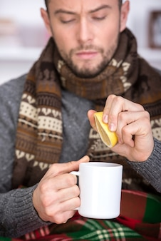 Il giovane bello sta bevendo il tè al limone.