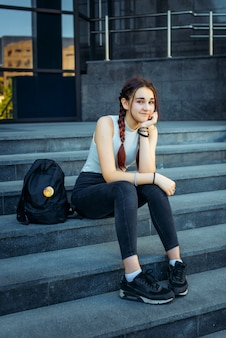 Il giovane bello studente che si siede sui punti si avvicina all'istituto universitario con lo zaino alla rientranza
