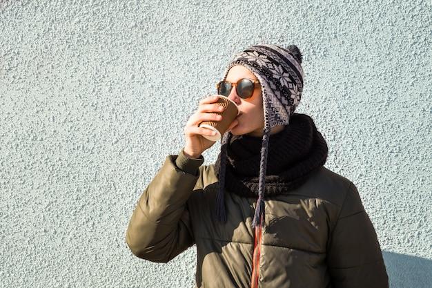Il giovane beve il caffè per andare dalla tazza di carta