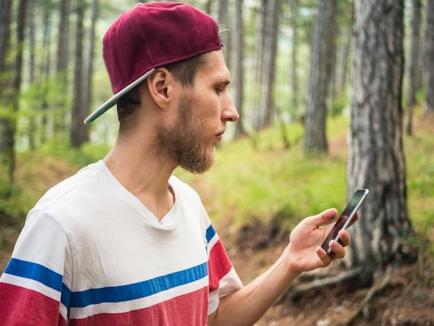 Il giovane blogger di hipster con la barba fa streaming dal vivo nella rete sociale che cammina nella foresta