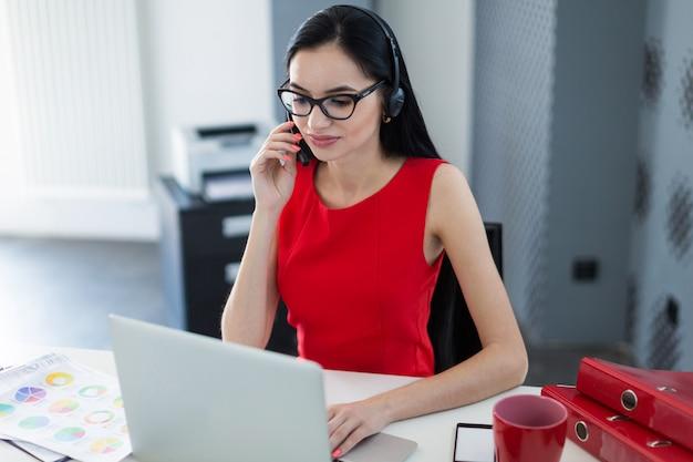 Il giovane businesslady attraente in vestito e vetri rossi si siede alla tavola e lavora con il computer portatile