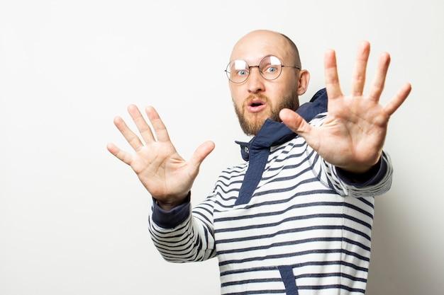 Il giovane calvo con la barba in vetri, un maglione con un cappuccio, chiude le sue mani dallo spettatore su bianco isolato. gesto fermati, continua, mantieni la distanza