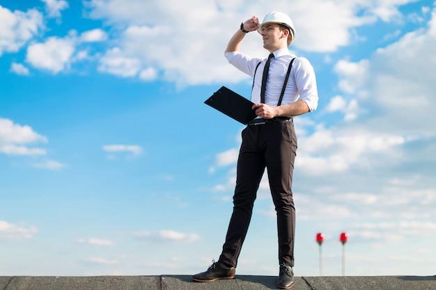 Il giovane caposquadra attraente in casco bianco, cravatta e bretelle sta sul tetto con tablet