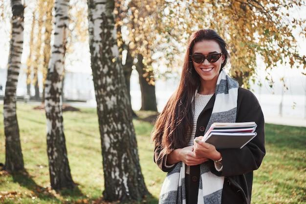 Il giovane castana sorridente in occhiali da sole sta nel parco vicino agli alberi e tiene il blocco note
