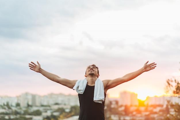 Il giovane che alza consegna il cielo del tramonto dopo l'allenamento