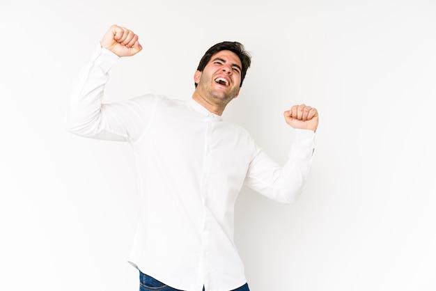 Il giovane che celebra un giorno speciale, salta e alza le braccia con energia.