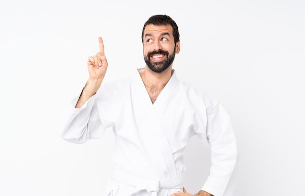 Il giovane che fa il karatè sopra bianco isolato che intende realizzare la soluzione mentre alza un dito su