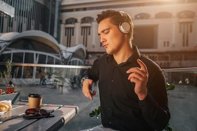 Il giovane che gode ascolta la musica tramite le cuffie. balla e saluta con le mani. guy si siede fuori al tavolo. il sole splende.