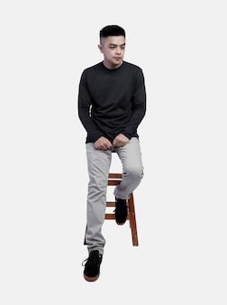 Il giovane che indossa la maglietta nera a maniche lunghe era seduto sulla sedia