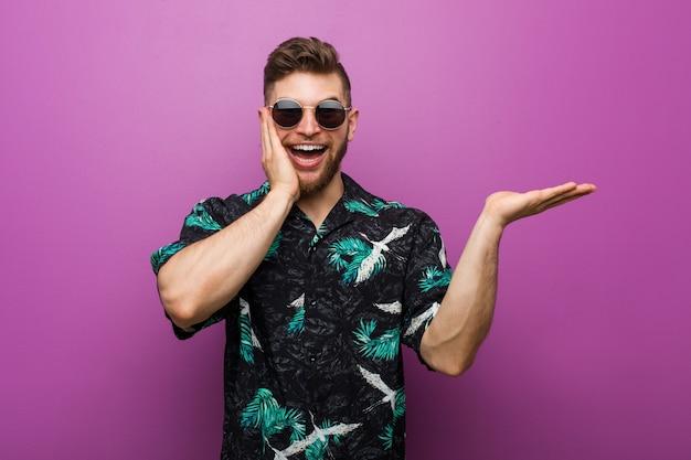 Il giovane che indossa un aspetto di vacanza tiene lo spazio della copia su una palma, tiene per mano la guancia.