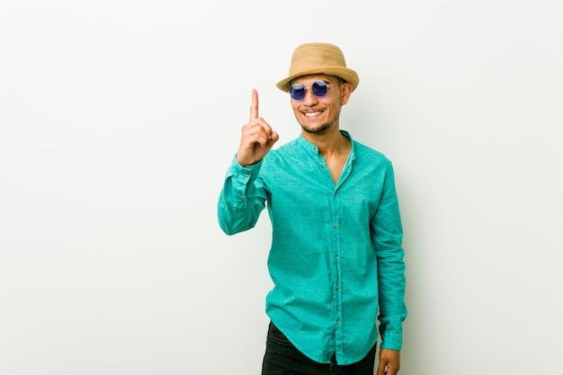 Il giovane che indossa un'estate copre la mostra del numero uno con il dito.