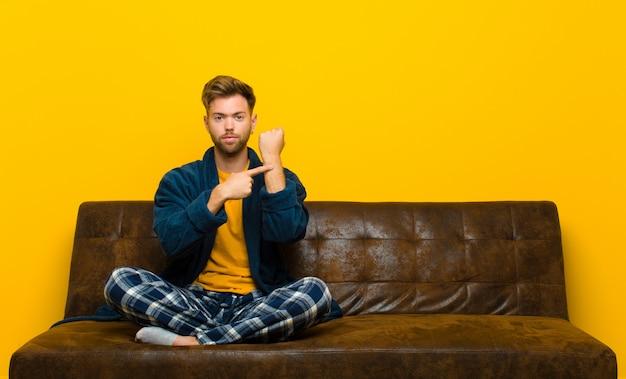 Il giovane che indossa un pigiama dall'aspetto impaziente e arrabbiato, indicando l'orologio, chiedendo puntualità, vuole essere puntuale. seduto su un divano