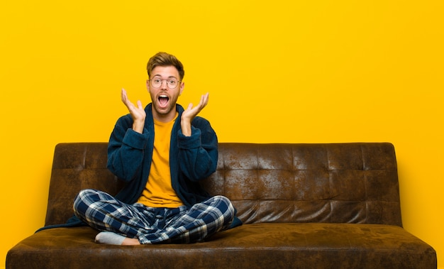 Il giovane che indossa un pigiama si sente scioccato ed eccitato, ridendo, stupito e felice a causa di una sorpresa inaspettata. seduto su un divano