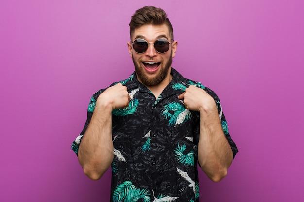 Il giovane che indossa una vacanza sembra sorpreso indicando se stesso, sorridendo ampiamente.