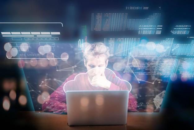 Il giovane che lavora alle icone e all'interfaccia futuristiche del computer portatile salta fuori dal dispositivo degli schermi