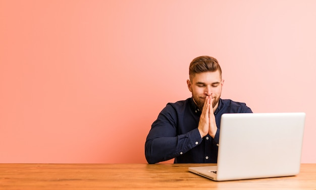 Il giovane che lavora con il suo computer portatile che si tiene per mano dentro prega vicino alla bocca, si sente sicuro.