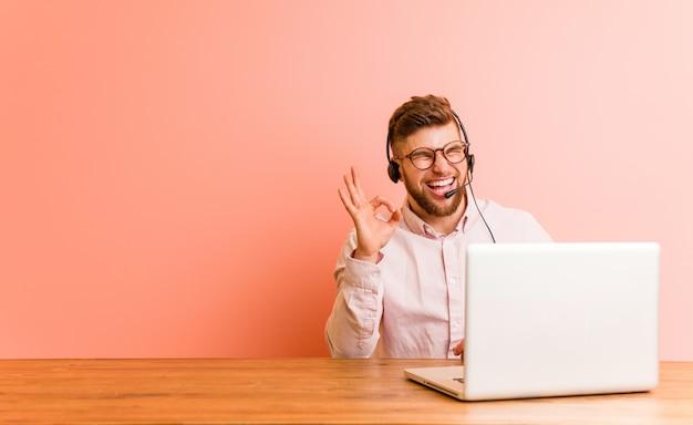 Il giovane che lavora in un call center strizza l'occhio e tiene un gesto ok con la mano.