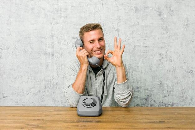 Il giovane che parla su un telefono d'annata fa l'occhiolino di un occhio e tiene un gesto giusto con la mano.