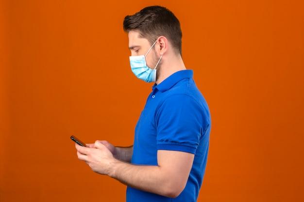 Il giovane che porta la camicia di polo blu nella maschera protettiva medica che sta lateralmente l'esame dello smartphone dentro consegna la parete arancio isolata