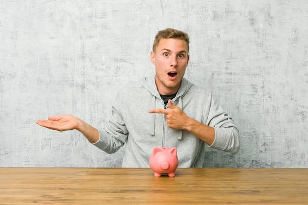 Il giovane che risparmia soldi con un porcellino salvadanaio ha eccitato la tenuta dello spazio della copia sulla palma.