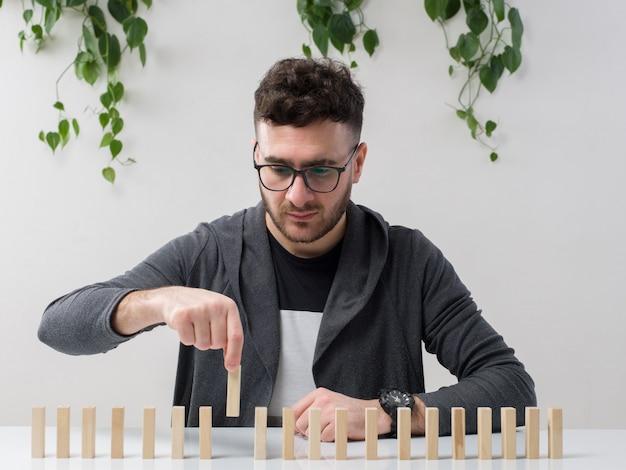 Il giovane che si siede in occhiali guarda la giacca grigia che gioca con le piccole figure di legno con la pianta su bianco